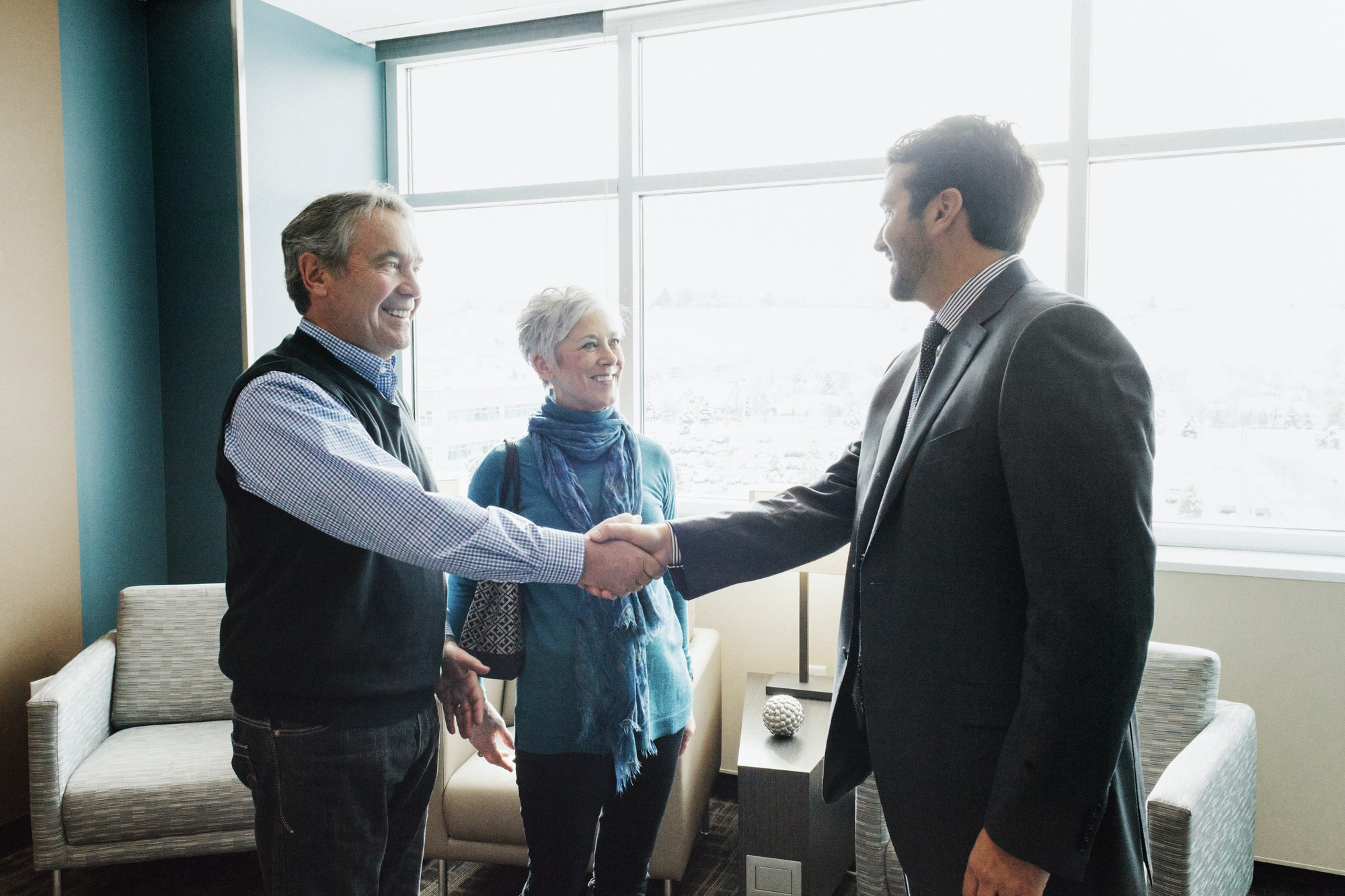 A man greeting a mature couple in an office.