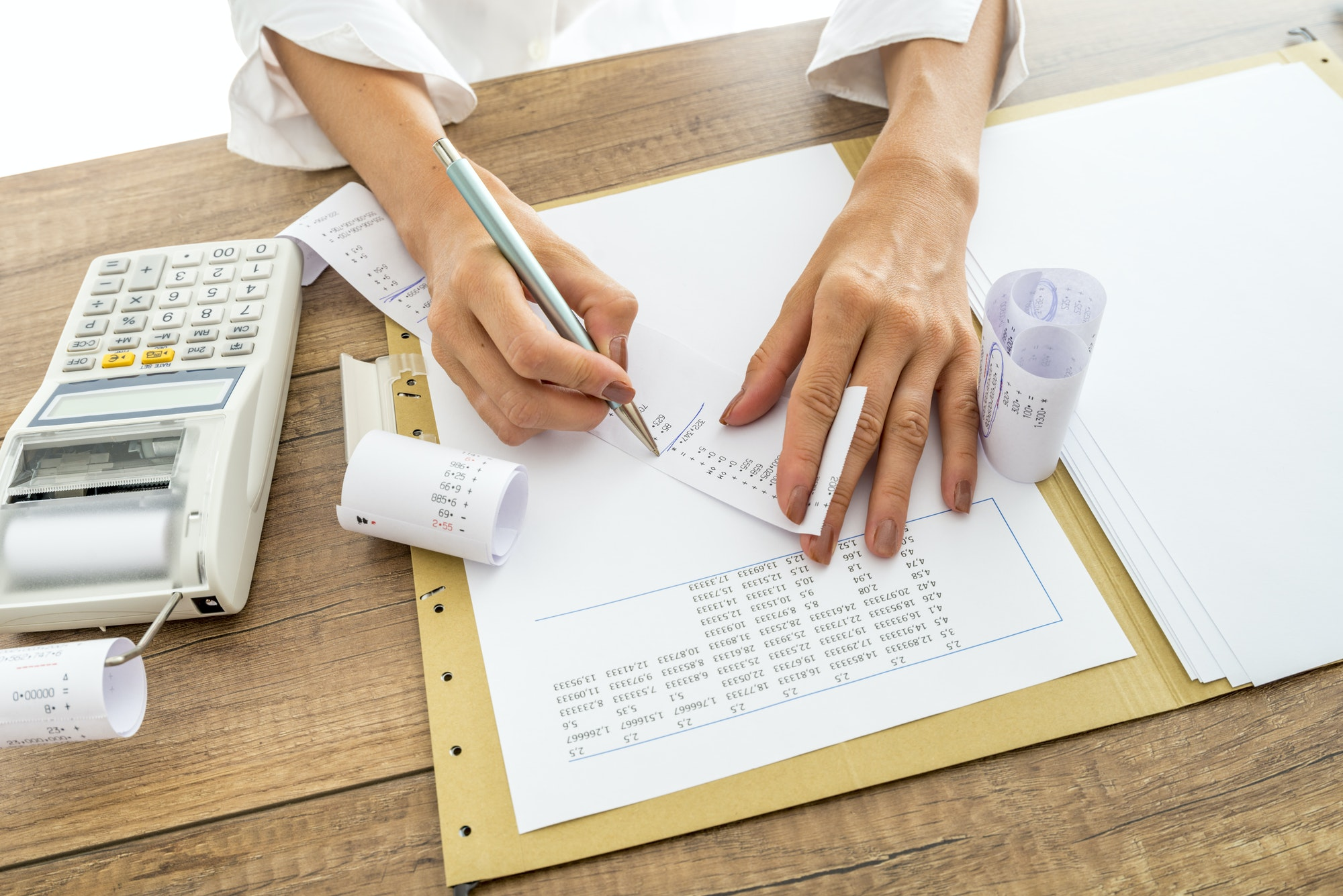 Accountant comparing receipts and statistical data while making a final report