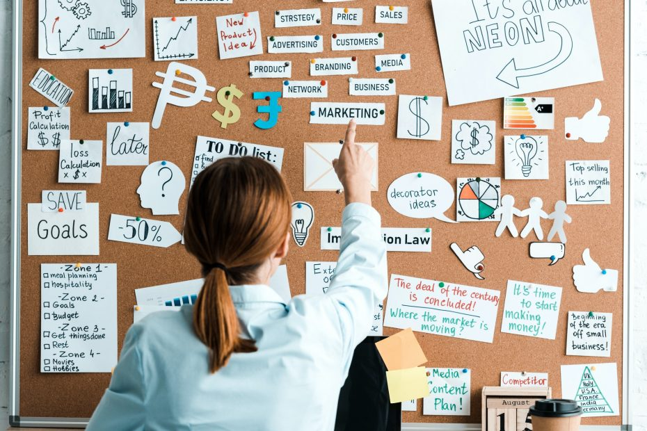 back view of businesswoman pointing with finger at marketing lettering on notice board