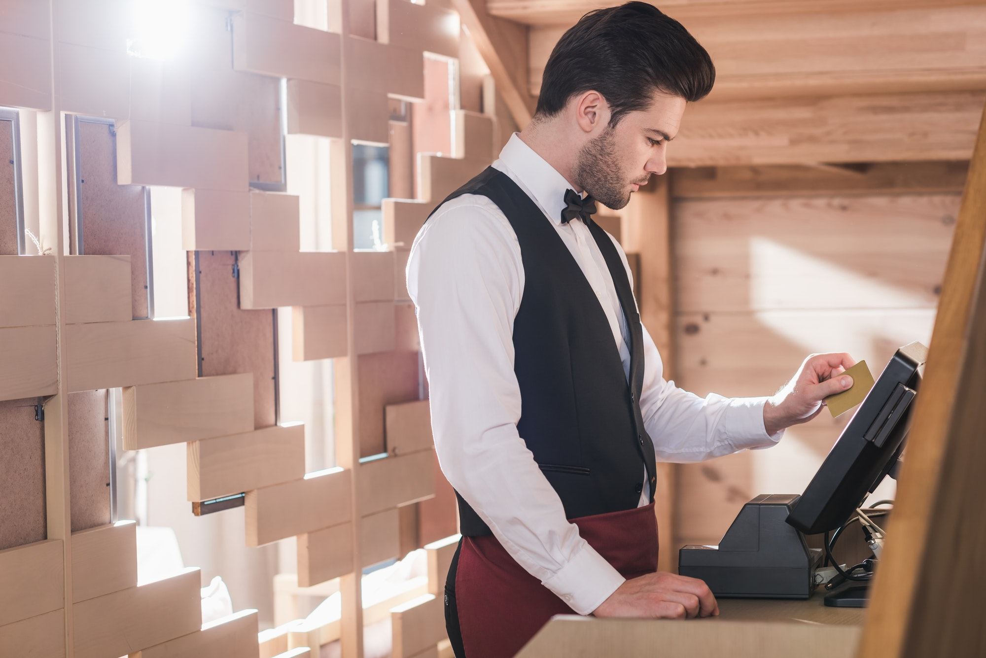 Waiter standing with credit card at cash register